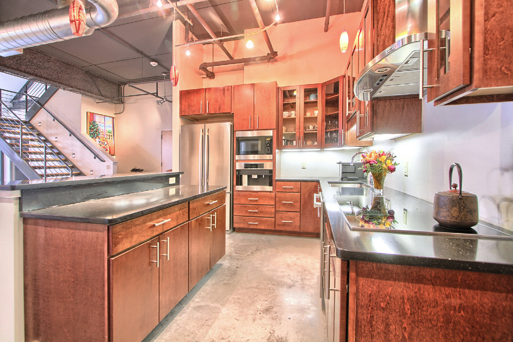 Customized Chef S Kitchen With Hardwood Cabinetry Glass Cabinet Doors And Silestone Countertops